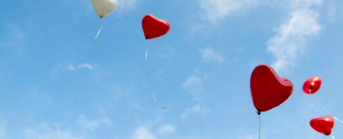 five heart balloons floating in a partly cloudy sky